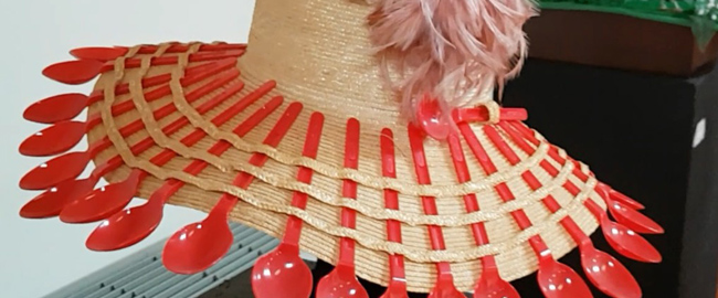 Strohhut mit orangefarbenen Plastiklöffeln aus dem Musseum der verrückten Hüte